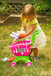 Toddler playing with doll baby outside.