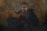 A masked male figure holding a young woman