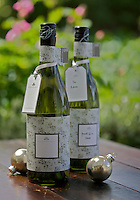 Photographed on a garden table are Christmas presents of two wrapped bottles of wine next to some silver baubles