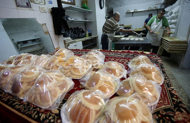 A Palestinian vendor prepares traditional pancakes known as ''Qatayef'' on the Muslim holy fasting month of Ramadan at his shop in the Old City of the West Bank town of Nablus on May 28, 2017. Ramadan is sacred to Muslims because it is during that month that tradition says the Koran was revealed to the Prophet Mohammed. The fast is one of the five main religious obligations under Islam. More than 1.5 billion Muslims around the world will mark the month, during which believers abstain from eating, drinking, smoking and having sex from dawn until sunset. Photo by Ayman Ameen