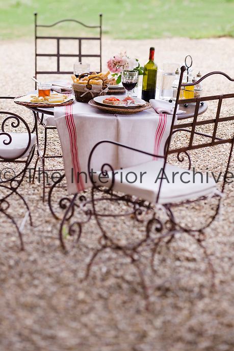 A simple lunch is elegantly presented on a wrought iron table in the garden of Relais Sant'Elena