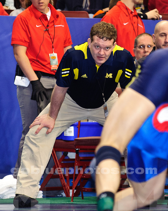 Michigan's coach Brian Dolph watches on as Anthony Biondo (197 lbs) wins by decision over Daniel Mitchell (American) 10-4 at the 2011 NCAA championships.