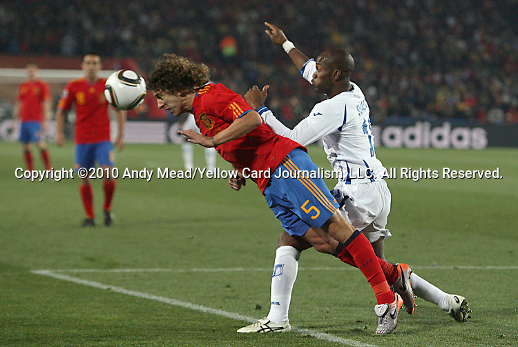 21 JUN 2010:  Carles Puyol (ESP)(5) is pushed by David Suazo (HON)(11) while heading the ball away from the box.  The Spain National Team defeated the Honduras National Team 2-0 at Ellis Park Stadium in Johannesburg, South Africa in a 2010 FIFA World Cup Group C match.