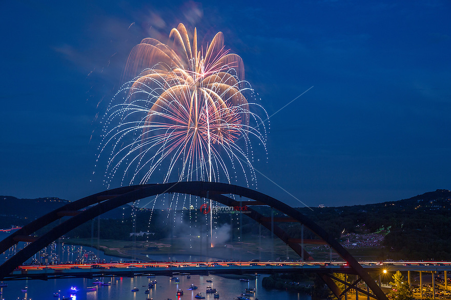 4th of July fireworks show towers over the 360 Bridge as boaters view on the waters of Lake Austin.