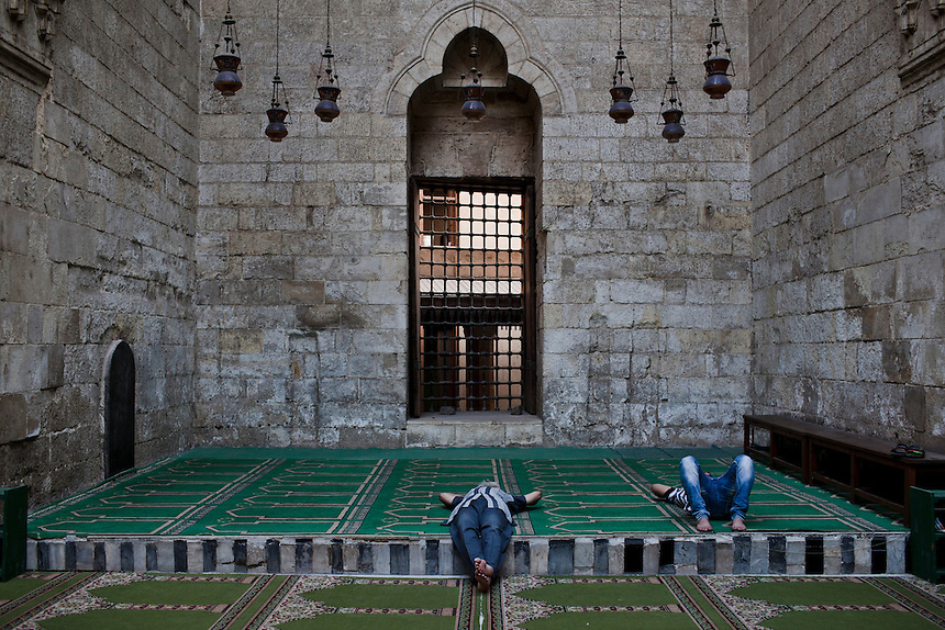 Two men sleep in a mosque in Islamic Cairo, one of the oldest areas of the city and a magnet for the millions of tourists that travel to Egypt each year, June 2012. Photo: Ed Giles.