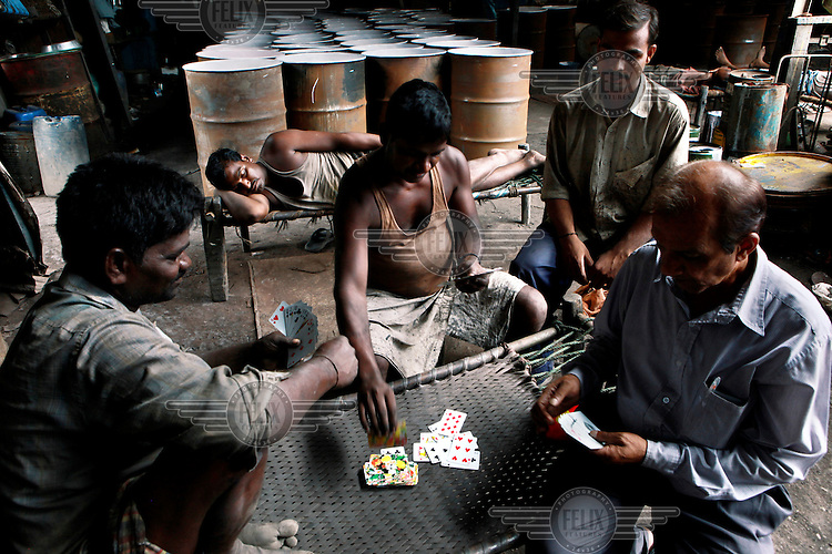 Men working in a recycling workshop playing cardsd during a break. They recycle used barrels by cleaning, burning, scraping and painting them. The waste recycling industry is helping thousands of slum dwellers out of poverty. The recycling of the discarded waste of Mumbai's 19 million citizens is a thriving business propelled by thousands of micro entrepreneurs. Economists estimate that the output of the slum is over 1 billion USD a year.