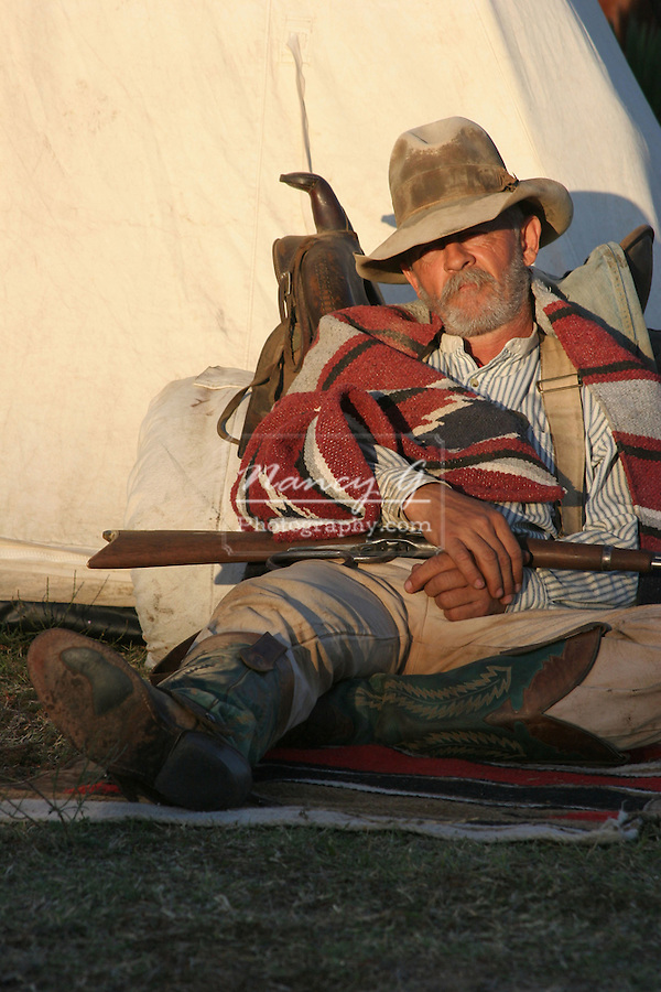 An old timer cowboy sleeping agains his tent at sunset