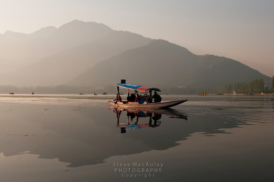 Traditional Kashmiri shikara on Dal Lake at sunrise, Srinagar, Kashmir, India.