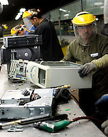12/4/2008 3:31:21 PM -- Seattle, WA.Nelson Andrade, 27, of of Seattle breaks down a computer separating the case from the motherboard and other metal components at Total Reclaim Inc., Environmental Services in Seattle Thursday Dec. 4, 2008.