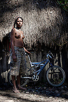 Otopina, 16 years old, stands with her bicycle near her house. Her father bought it for 500,000 Rupiah (GBP 26.45). Otopina shares the bicycle with all the children from her village.