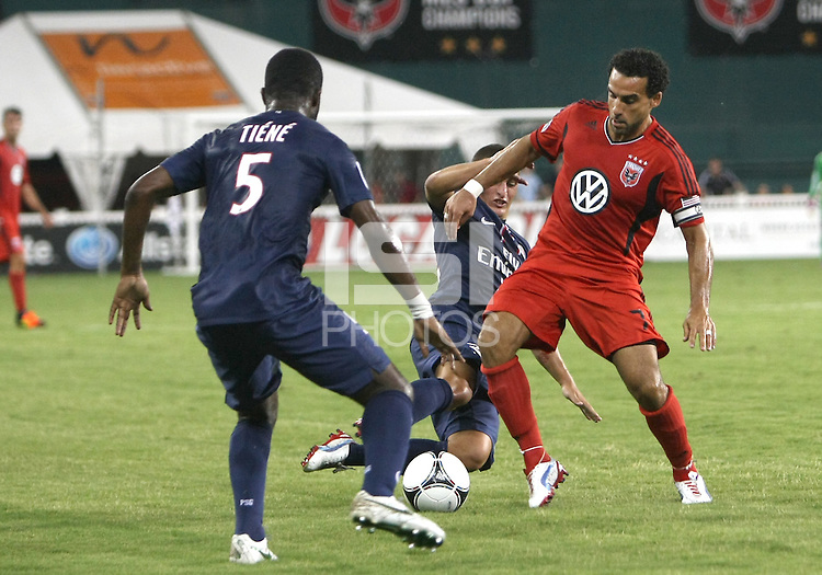 WASHINGTON, DC - July 28, 2012:  Dwayne DeRosario (7) of DC United is tackled by Mathieu Bodmer (12) of PSG (Paris Saint-Germain) in an international friendly match at RFK Stadium in Washington DC on July 28. The game ended in a 1-1 tie.