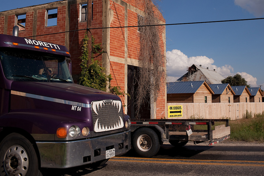 SEPTEMBER 26, 2013 - RUNGE, TX: A heavy truck passes by on a small road in the town of Runge, Texas. In the background is an old abandoned building next to new cabins which temporarily house oil field workers. CREDIT: Lance Rosenfield/Prime