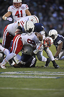 23 November 2013:  Penn State LB Brandon Bell (26) and S Malcolm Willis (1) hit Nebraska RB Ameer Abdullah (8) .The Nebraska Cornhuskers defeated the Penn State Nittany Lions 23-20 in overtime at Beaver Stadium in State College, PA.
