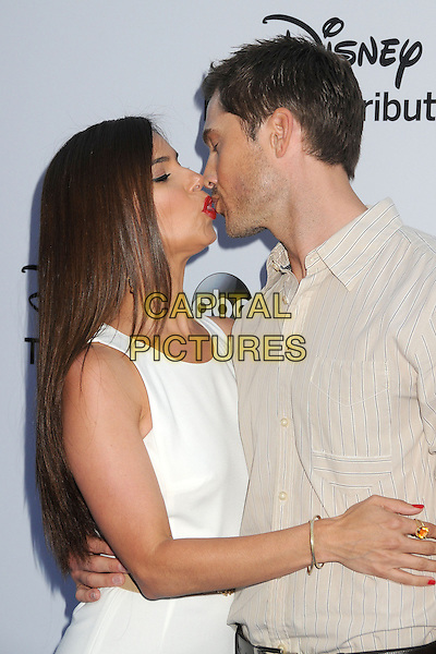 Roselyn Sanchez, Eric Winter.Disney Media Networks International Upfronts 2013 held at Walt Disney Studios, Burbank, California, USA..May 19th, 2013.half length jumpsuit brown trousers shirt profile kiss kissing married husband wife side  white sleeveless  .CAP/ADM/BP.©Byron Purvis/AdMedia/Capital Pictures