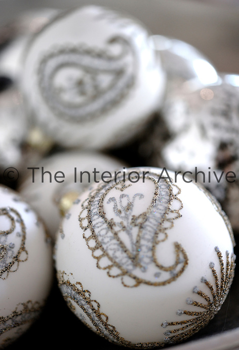 Paisley patterned Christmas baubles shimmer in a bowl