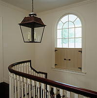 Outdoor-style half shutters dress the arched window above the staircase