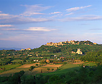 Tuscany, Italy      <br /> Fields and vineyards in the rolling hills beneath the hilltown of Montepulciano and San Biagio church in the Val d'Orcia