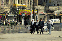 Man and three women dressed in traditional clothing walk down a street, Amman, Jordan.