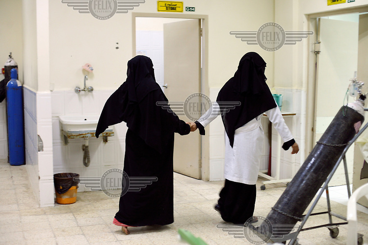 A female patient is led through the maternity unit at Sayoun General Hospital. This is the only hospital for the entire district. Patients here usually have to pay for both treatment and medicines, but babies are delivered free of charge.