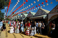 Women in flamenco dress during the Seville Spring Fair in the Los Remedios district, Seville, Andalusia, Spain.