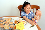 7 year old girl sitting at table talking to dolls to distract herself from the temptation of eating forbidden cookies horizontal Hispanic Dominican