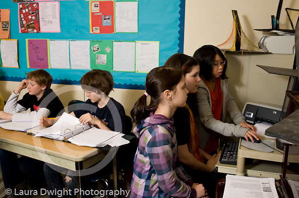 Public Middle School Grade 6 girls using computer and Grade 7 students in math class horizontal