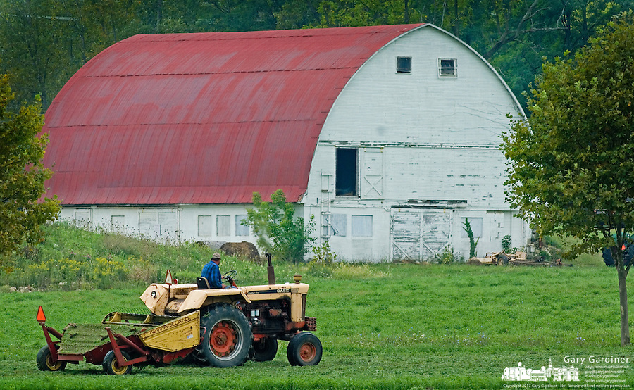 Farmer runs a cutter through a field as he makes his fourth  hay cut for the season on a small farm plot in Westerville, Ohio.<br />