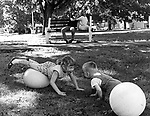 Two children playing in foreground, as two teenagers communicate in background at denton Green Park in Hempstead, NY in June 1968. Photograph by Jim Peppler. Copyright Jim Peppler 1968.
