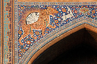 "Detail of solar tiger mosaic, Sher-Dor Madrasah, 1619-36, Samarkand, Uzbekistan, pictured on July 15, 2010 at sunset which lights up the elaborately tiled facade. The Sher-Dor Madrasah, commissioned by Yalangtush Bakhodur as part of the Registan ensemble, and designed by Abdujabor, takes its name, ""Having Tigers"", from the double mosaic (restored in the 20th century) on the tympans of the portal arch showing suns and tigers attacking deer. Samarkand, a city on the Silk Road, founded as Afrosiab in the 7th century BC, is a meeting point for the world's cultures. Its most important development was in the Timurid period, 14th to 15th centuries. Picture by Manuel Cohen."