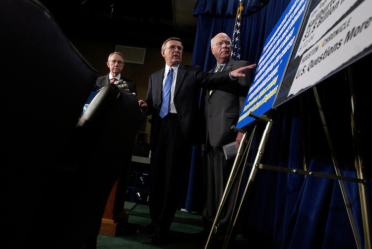 Sen. Byron Dorgan, D-N.D., reads a quote from an official from the Corps of Engineers, during a news conference with Senate Minority Leader Harry Reid, D-Nev., left, and Sen. Pat Leahy, D-Vt., to introduce legislation to implement major reforms in government contracting.  The proposals would put in place tough penalties for war profiteers, crack down on corporate cheaters and force competition in the award of government contracts.