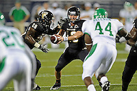 1 September 2011:  FIU quarterback Wesley Carroll (13) hands off the ball to running back Darriet Perry (28) in the second quarter as the FIU Golden Panthers defeated the University of North Texas, 41-16, at FIU Stadium in Miami, Florida.