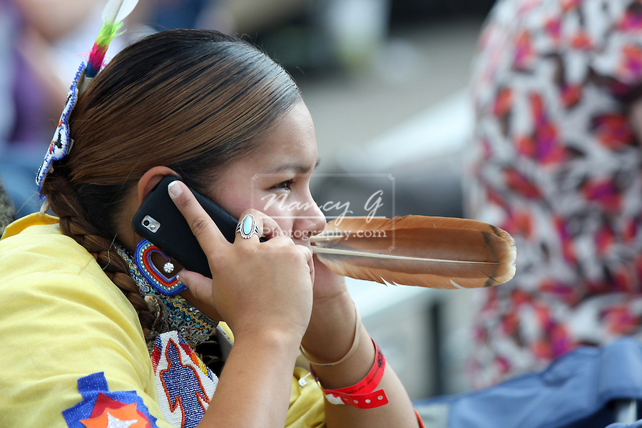 A teenager female Native American Menomonee Indian dancer talking on a cell phone at a Pow Wow at the Milwaukee Lakefront Indian Summer Festival, Wisconsin