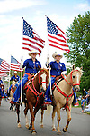 Horse riders carry U.S. flags during the Saturday, June 7 parade in Iron River, Mich. The riders were also in the U.P. Championship Rodeo the same weekend at Iron River.