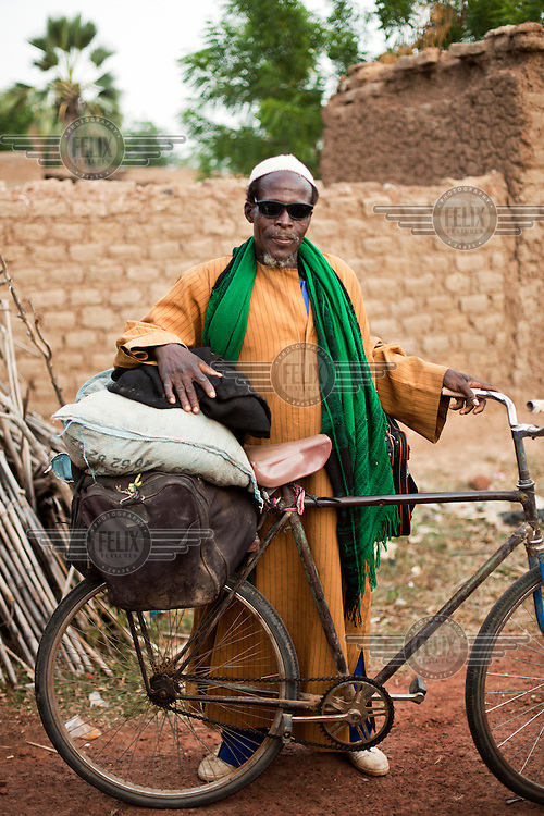 A man stands with his bicycle in Karaba.