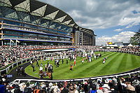 A large crowd waits for the horses in the next race to parade round the parade ring and saddling up enclosure at Ascot Race Course during Royal Ascot Week.