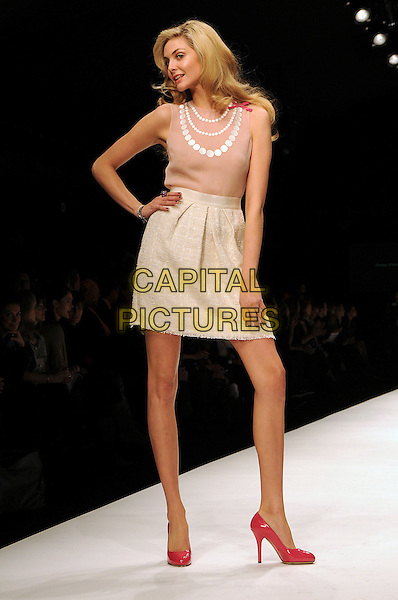 TAMSIN EGERTON.The Fashion For Relief Haiti 2010 show for London Fashion Week Autumn/Winter 2010 at Somerset House, London, England..February 18th, 2010.LFW catwalk runway full length beige skirt pink sleeveless top red shoes hand on hip circles collar .CAP/CAS.©Bob Cass/Capital Pictures.