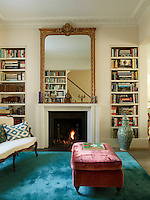 Built-in bookshelves flank a contemporary fireplace topped with a gilt-framed mirror in one half of the double living room