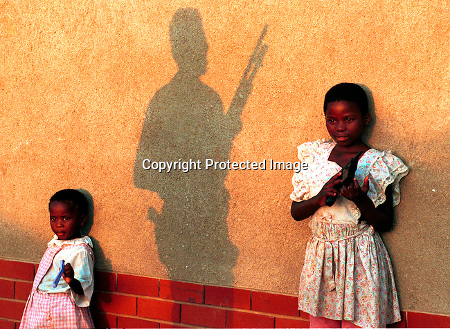 dippchi00097 Children protected by military men at a church in Lindelani, South Africa. Their family's are ANC supporters and they fled from violent clashes with the IFP (Inkatha freedom party) days before the first democratic election in South Africa on February 27, 1994;two girls standing against a wall; shadow of soldier with gun..©Per-Anders Pettersson/iAfrika Photos