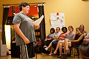 Onlookers listen to Ian McKeown spit during a community wide poetry open mic presented by the Sacrificial Poets at Flyleaf Books in Chapel Hill, N.C., Wednesday, July 6, 2011.