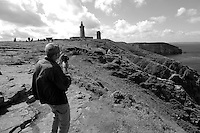 Man filming the lighthouse at Cap Fréhel, Brittany, France.
