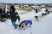 David Walker, from Holy Cross, in Shageluk to enjoy the Iditarod helps Bob Bundtzen maneuver his dogs out of the Shageluk checkpoint on Saturday morning    Iditarod 2009