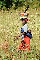 MALI, Bougouni, cotton and sorghum field, woman with machete and enamel bowl on the head going with child to her farmwork / Frau mit Emaille Schale auf dem Kopf geht mit Kind zur Feldarbeit