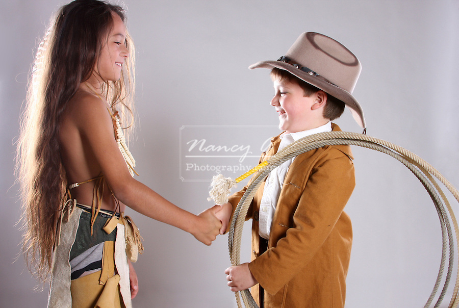A cowboy and Indian greet with a handshake