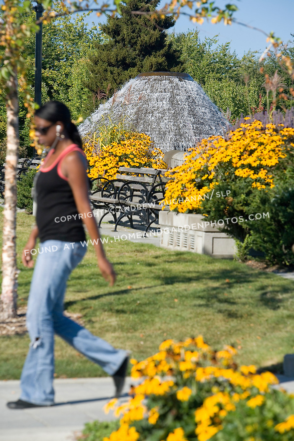A woman walks through an urban park on a sunny fall day.