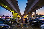 Bellmore, New York, USA. August 24, 2018. At the Bellmore Friday Night Car Show, many cars and visitors are under the overhead tracks at the Bellmore LIRR train station.