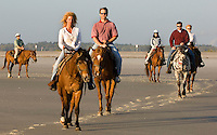 A group of people ride horses along the beach in Amelia Island, FL