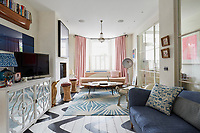 In the sitting room, natural materials are mixed with cheerful colour. The floor has a graphic black and white hand-painted effect and contrasts with the patterned rug. Interior glass doors allows natural light to come in from the hallway.