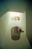 A woman lowers a basket of washing on a pulley down from the roof