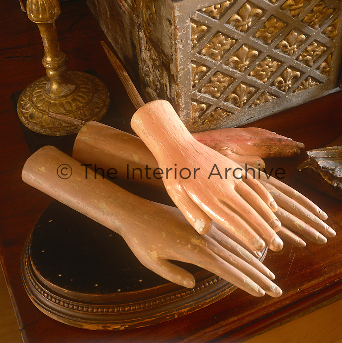 Two pairs of plaster hands ar displayed on a table.