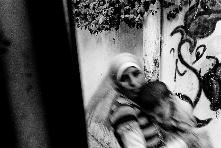 Holding her child, a Palestinian mother runs through a laneway during clashes between Israeli soldiers and Palestinian youths at Qalandiya, The West Bank, October 2009. Photo: Ed Giles.